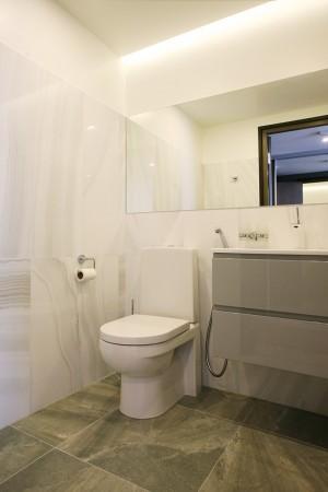 vannitoa-mööbel-valge-tualettpott-tumedal-põrandal